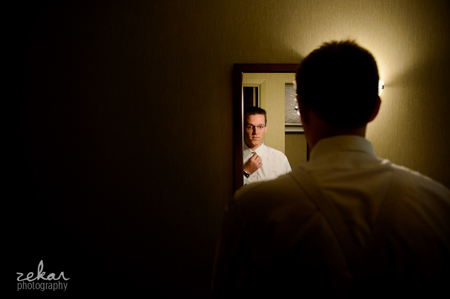 groom putting tie on in mirror