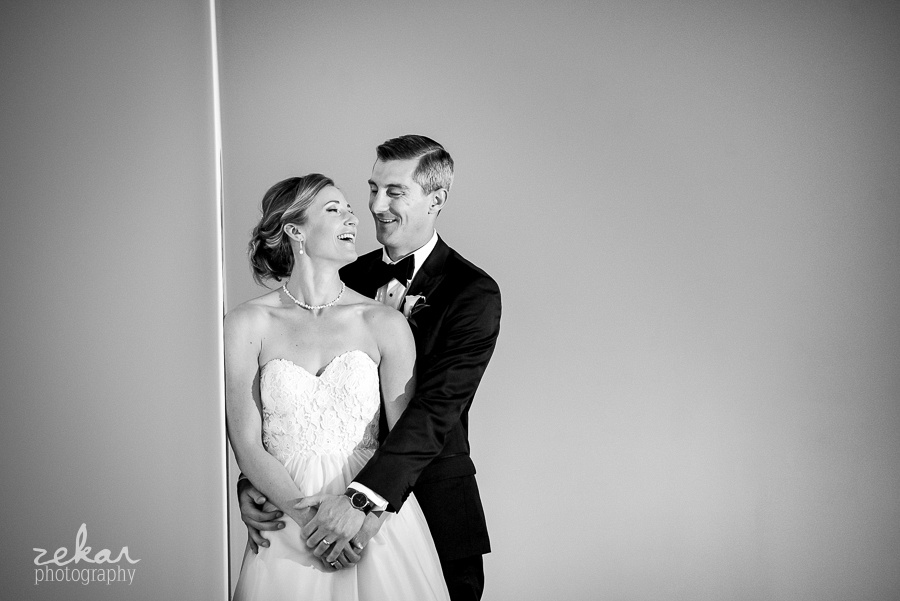 bride and groom laughing in white room