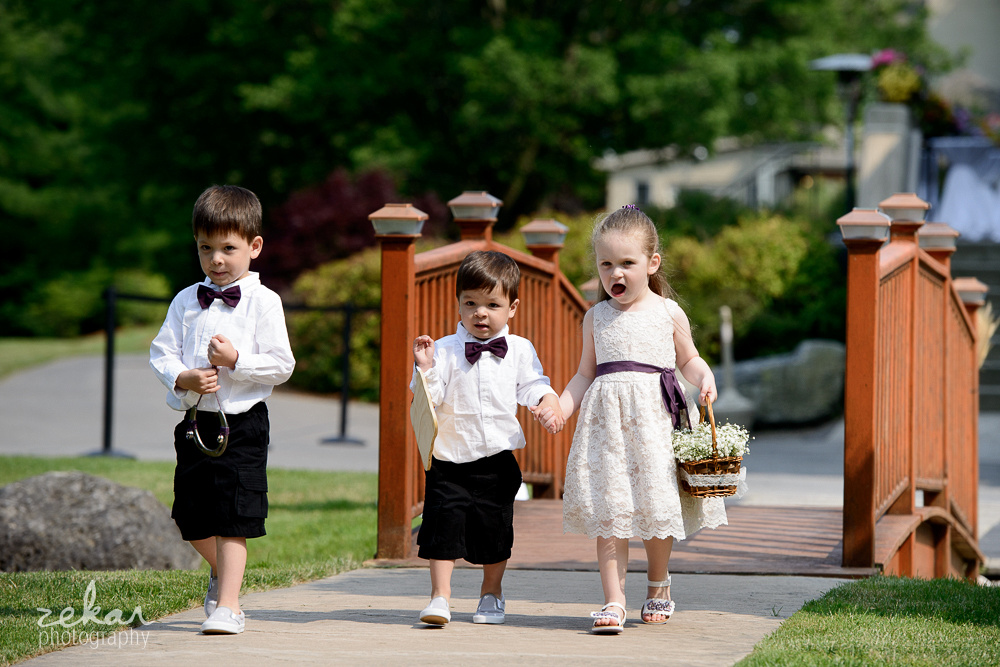 flower girl and ring bearers walking over bridge