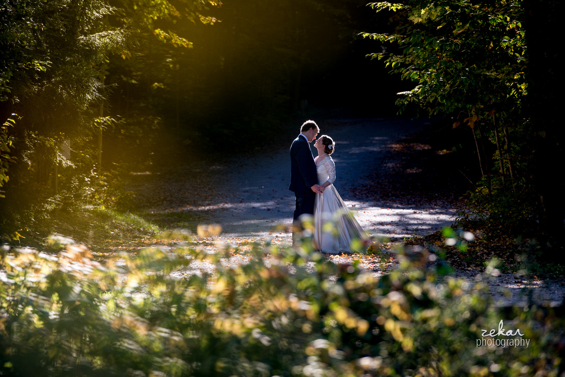 bride and groom kissing on wooded trail