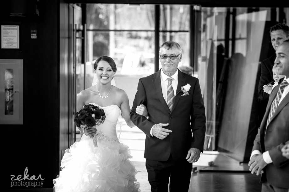 black and white photo bride walking down aisle