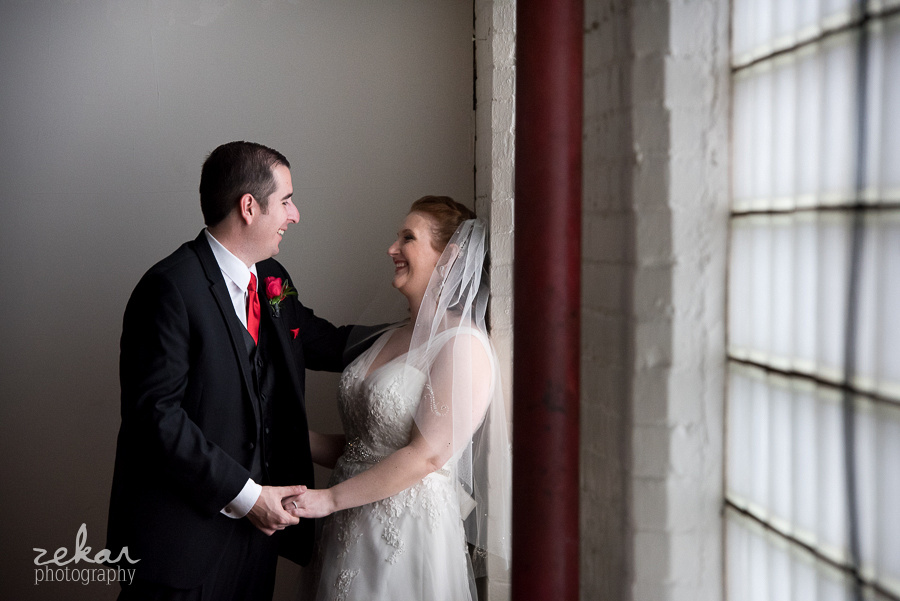 bride and groom against wall
