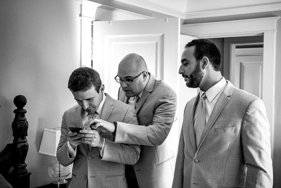 groom looking at iphone