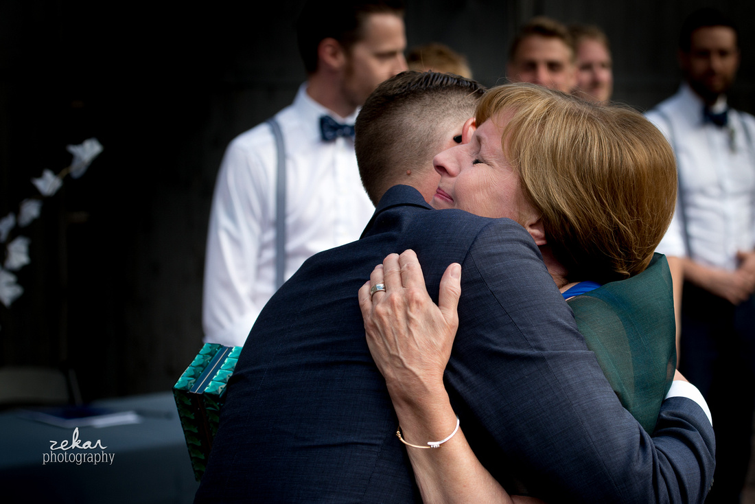 mother hugging groom at aisle