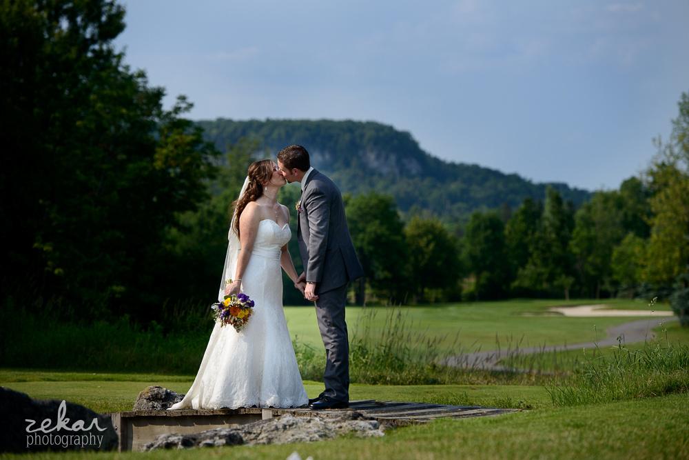 couple kissing next to escarpment