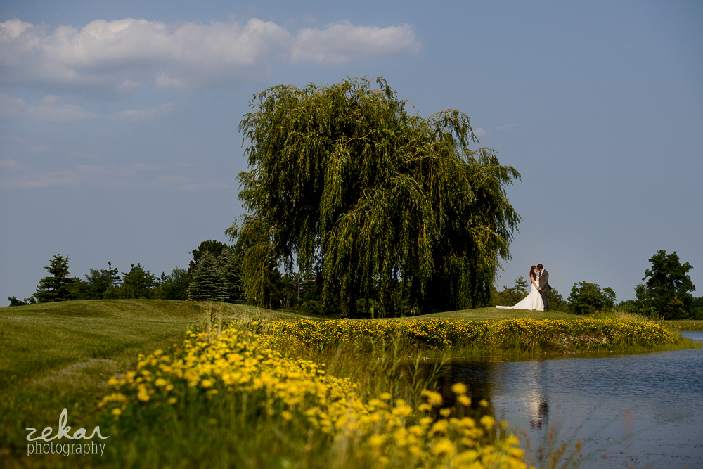 couple kissing by pond with yellow flowers
