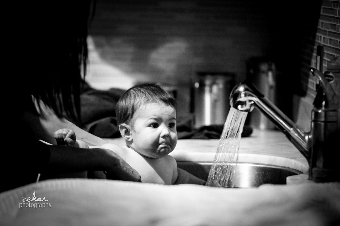 black and white photo of baby in bath