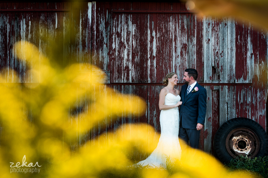 bride and groom looking at eachother in barn