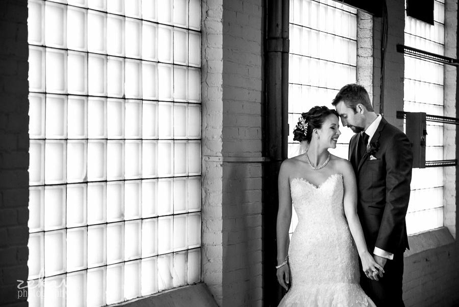 bride and groom pose by glass bricks
