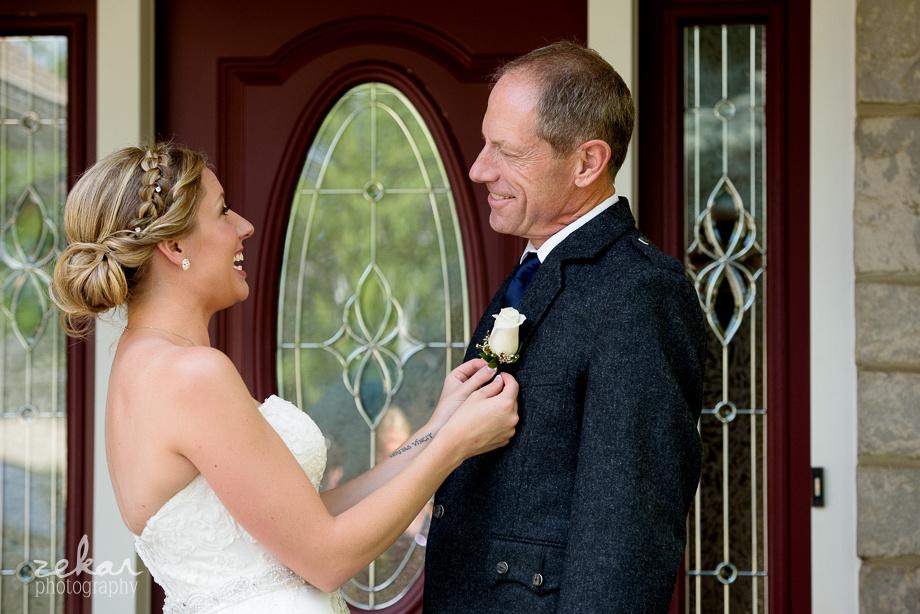 bride pinning corsage to dad