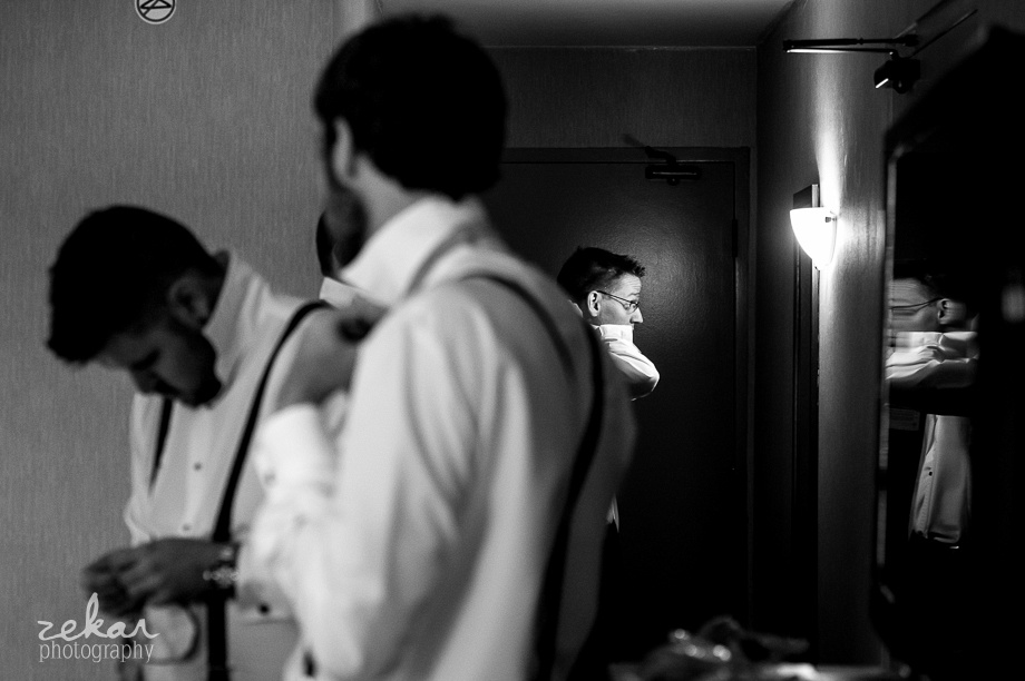 black and white picture of groom getting ready