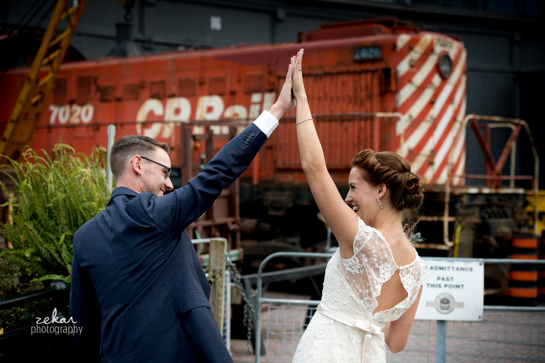 bride and groom high-five beside train