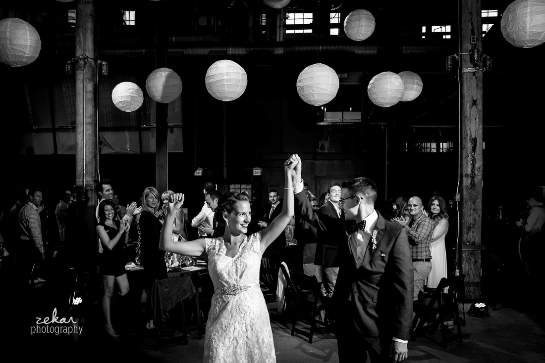 black and white photo of bride and groom entering reception