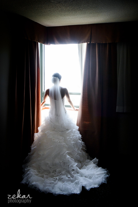 silhouette bride looking out hotel room
