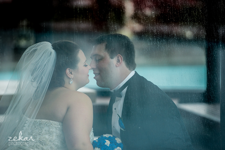 bride and groom kissing in rainy window