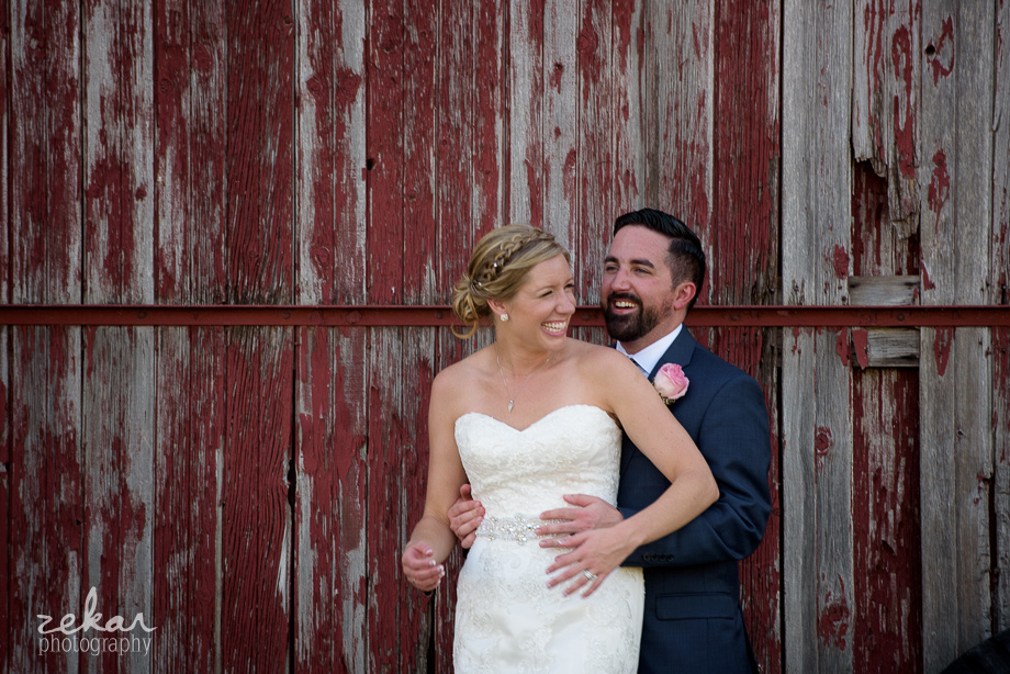 couple laughing by barn wall